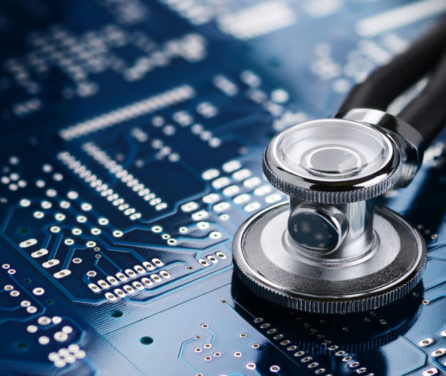 Medical stethoscope on the blue printed circuit board. Repair diagnostic fixing electronic concept