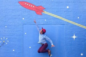 Picture of a man jumping in the air and trying to reach a wall painting showing a rocket